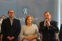 Dwóch mężczyzn pomiędzy nimi kobieta, na tle herbu gminy Świebodzice, mężczyzna po prawej z mikrofonem