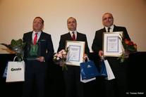 Trzech mężczyzn w garniturach z torbami prezentowymi, tabliczkami i kwiatami