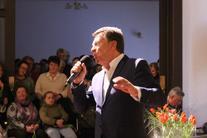 Mężczyzna z mikrofonem pomiędzy kobietami
