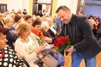 Grupa ludzi na publiczności- wręczenie kobietom kwiatów