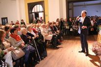 Mężczyzna z mikrofonem, z lewej strony publiczność