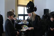 Kobieta z czapką górnika wręczająca chłopcu upominek