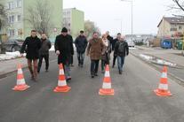 Grupa ludzi na drodze, na pierwszym planie dwa żółte pachołki