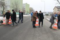 Grupa ludzi na drodze, zdejmowanie żółtych pachołków