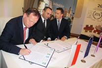 Trzech mężczyzn, jeden podpisuje dokumenty