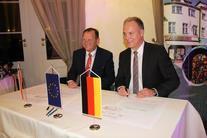 Dwóch mężczyzn przed nimi miniaturki flag: niemiecka i Unii Europejskiej