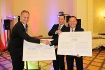 Trzech mężczyzn, 2 podaje sobie ręce, trzymają duże plakaty