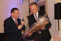Dwaj mężczyźni przy mikrofonie trzymający upominek