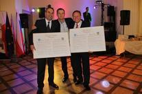 3 mężczyzn trzymający Akt zawarcia Partnerstwa, ściskających wzajemnie dłonie