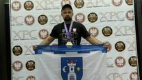 Bartłomiej Rogoziński Mistrz Europy i Świata w wyciskaniu sztangi leżąc prezentuje flagę Świebodzic