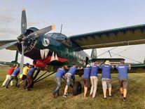 Uczestnicy pikniku przy samolocie, napierający na jego skrzydła