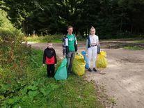 Uczestnicy biorący udział w akcji, z pełnymi workami śmieci