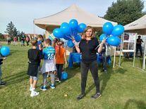 Kobieta trzymająca w obu rękach niebieskie balony, wtle kolejka dzieci