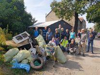 Uczestnicy akcji przy stercie zebranych śmieci (worki ze śmieciami, stare opony, umywalka, wózek sklepowy itp.)