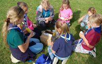 Grupa dzieci siedzących na trawie otwierających pudełko
