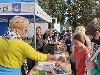 Uczestnicy częstujący się słodyczami przy namiocie z napisem www.swiebodzice.pl
