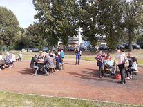 Uczestnicy wydarzenia siedzący przy stołach na boisku