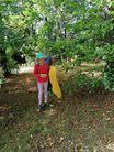 Dziewczynka pośród drzew trzymająca żółty worek
