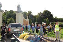 Uczestnicy biorący udział w akcji przy samochodzie z przyczepką na której leżą worki ze śmieciami