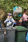 Chłopiec trzymający śmieci na kiju przy kontenerach na śmieci