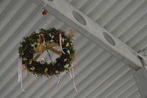 Na zdjęciu widać zawieszoną pod dachem wiechę budowlaną w kształcie wieńca.