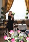 Na zdjęciu widać kobietę w czarnej sukience mówiącą do mikrofonu
