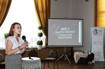 Na zdjęciu widać kobietę i ekran z wyświetloną prezentacją