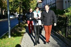 Uczestnicy odbioru remontu idą chodnikiem przy ulicy Aleje Lipowe.