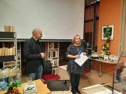 Dyrektor Biblioteki i autor książki Mariusz Kurc stoją przy stoliku w Miejskiej Bibliotece Publicznej.