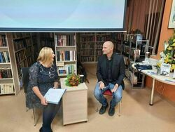 Dyrektor Biblioteki i autor ksiązki Mariusz Kurc siedzą  przy stoliku w Miejskiej Bibliotece Publicznej.