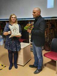 Dyrektor Biblioteki przekazuje upominek Mariuszowi Kurcowi.