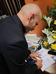 Mariuszem Kurcem podpisujący swoją autorką książkę.