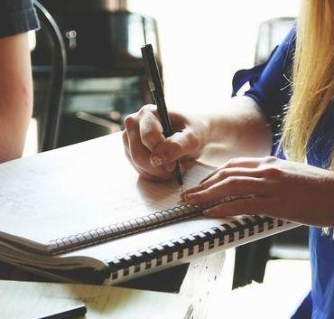Na zdjęciu osoba pisząca w zeszycie.