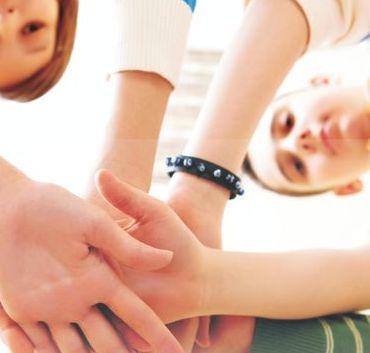 Wykadrowana część plakatu, osoby trzymające się za ręce, tworzące team.