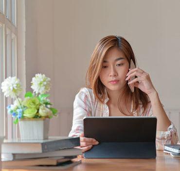 Osoba rozmawiająca przez telefon i patrząca się w laptopa