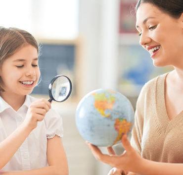 Dziecko podczas oglądania globusa lupą wraz z nauczycielką