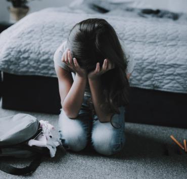 Płaczące dziecko siedzące na dywanie