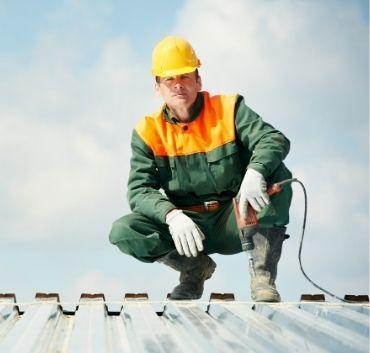 Robotnik na dachu z wiertarką