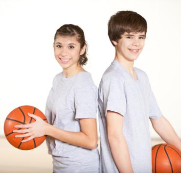 Dziewczyna i chłopak stojący plecami do siebie, trzymają piłki koszykowe