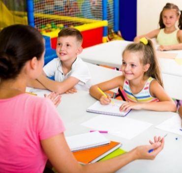 Uśmiechnięte dzieci w szkole z nauczycielką