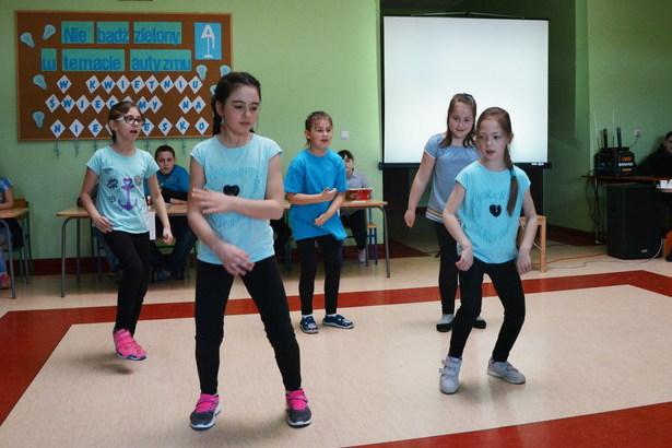 Zdjęcie przestawia występ dzieci w niebieskich koszulkach