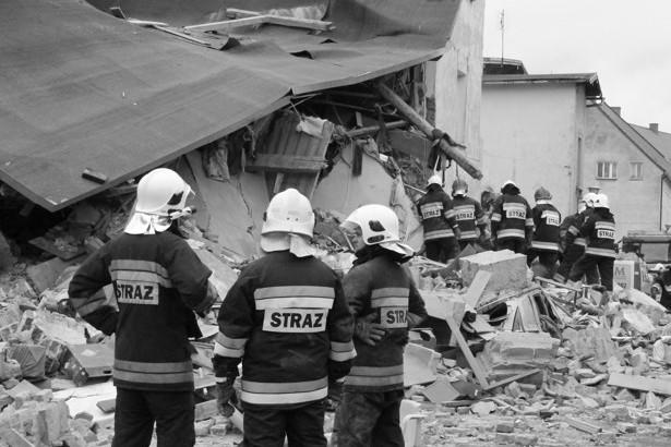 Zdjęcie strażaków  i gruzów budynku