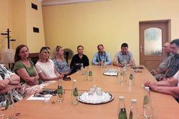 Na zdjęciu osoby siedzące przy stole