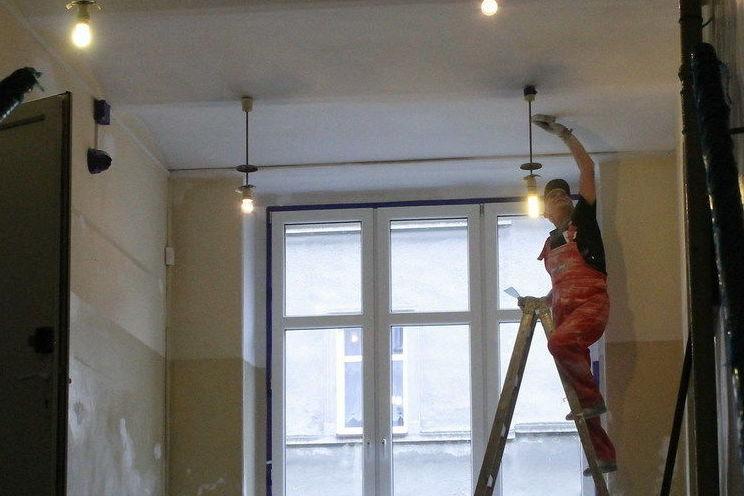 Zdjęcie robotnika na drabinie podczas remontu sufitu