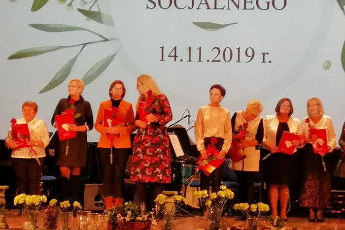 Zdjęcia z obchodów dnia pracownika socjalnego. Osiem kobiet przy kwiatach i z dyplomami w rekach