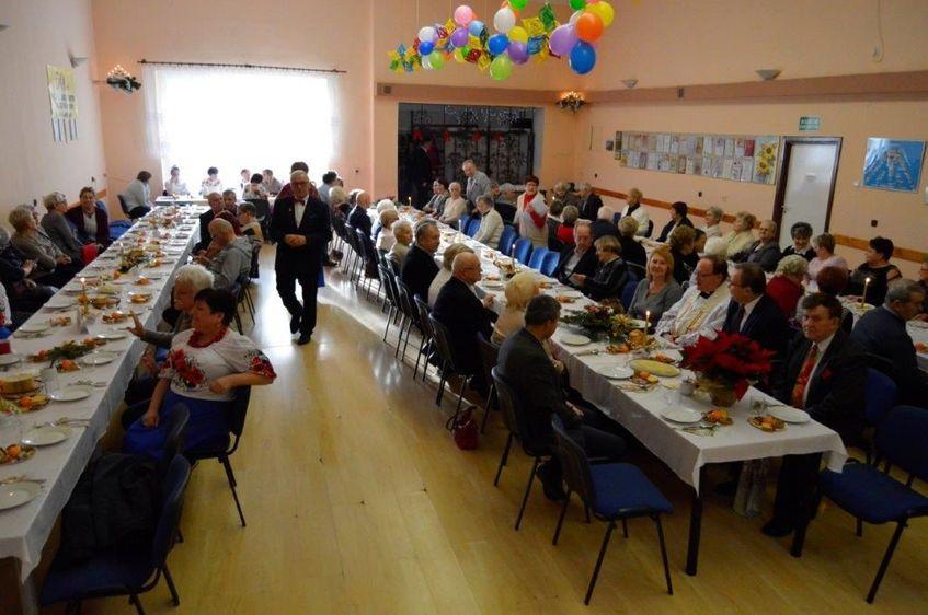 Spotkanie wigilijne, dwa stoły z jedzeniem wokół uczestnicy spotkania