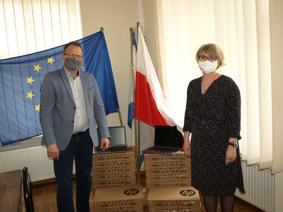 Burmistrz miasta Świebodzice Paweł Ozga stojący z jedną z Pań dyrektorek na tle paczek z komputerami
