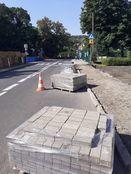 Zdjęcie przedstawia materiały budowlane ustawione na ulicy i pachołek ostrzegawczy