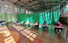 Zdjęcie przedstawia reprezentantów organizacji pozarządowych podczas głosowania. Na zdjęciu widać cztery kobiety siedzące w sali gimnastycznej przy ławkach. Z tyłu widoczna jest zielona zasłona.