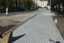 Zdjęcie przedstawia chodnik w trakcie remontu  wykonany z kostki brukowej.